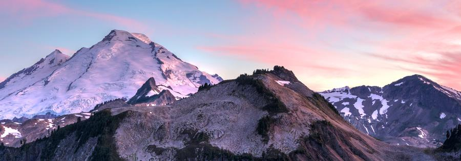 Snowy mountain tops against a sunset background.