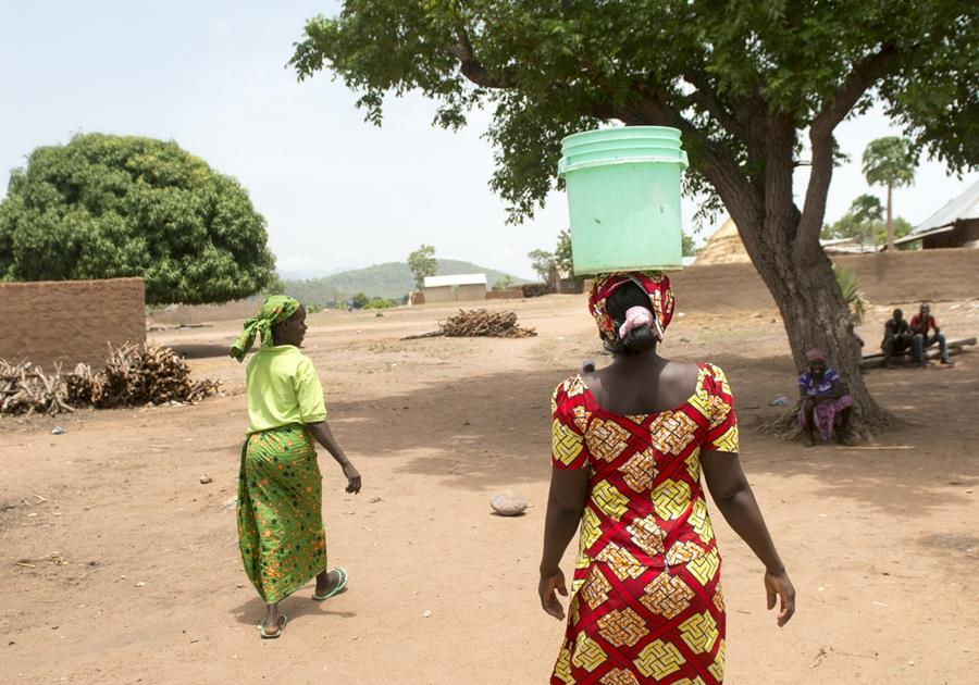 Woman carrying water pail on her head