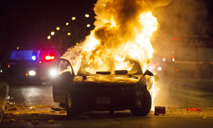 A car burns as a crowd of more than 100 people gathered following the fatal shooting of a man in Milwaukee.