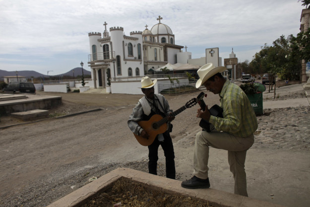A city in northern Mexico where many drug kingpins are buried is pleading with people not to sing narcocorridos — songs glorifying cartels — while partying this year.